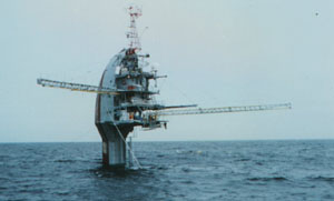 FLIP, a ship which can be partially submerged to form a fixed instrument platform, is shown in its buoy position supporting masts of instruments.